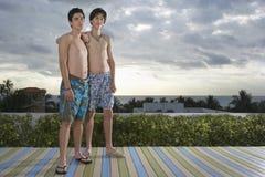Amis adolescents se tenant sur l'océan de négligence de plate-forme Photographie stock libre de droits