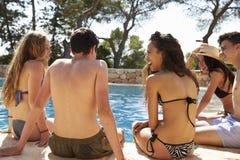 Amis adolescents traînant près d'une piscine, vue arrière Photo stock