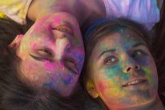 Amis adorables couverts de peinture Holi, se trouvant sur l'asphalte Photo stock