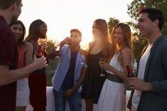 Amis adultes ayant une vie sociale à une partie sur un dessus de toit au coucher du soleil Image libre de droits