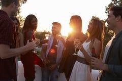 Amis adultes ayant une vie sociale à une partie sur un dessus de toit au coucher du soleil Photographie stock libre de droits
