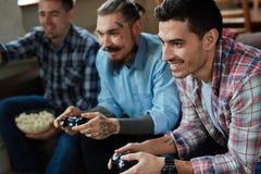 Amis adultes jouant des jeux vidéo sur le divan Images libres de droits