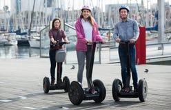 Amis adultes posant près des segways sur le rivage Photo libre de droits