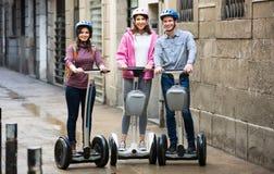 Amis adultes posant sur des segways sur la rue de ville Photographie stock libre de droits