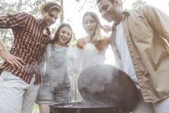 Amis affamés faisant cuire le barbecue dehors Photo libre de droits