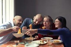Amis affamés mangeant des spaghetti Images stock