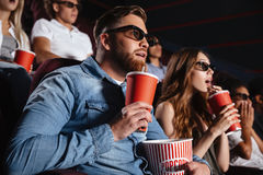 Amis affectueux concentrés de couples s'asseyant dans le cinéma Images libres de droits