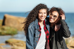 Amis africains de sourire de femme marchant dehors à la plage Images stock