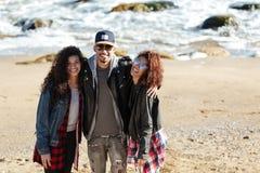 Amis africains de sourire marchant dehors à la plage Photo libre de droits