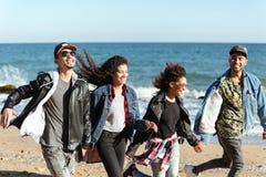 Amis africains de sourire marchant dehors à la plage Images libres de droits