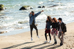 Amis africains heureux marchant dehors à la plage Image libre de droits