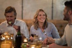 Amis agissant l'un sur l'autre tout en dinant dans le restaurant Photos libres de droits