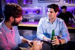 Amis agissant l'un sur l'autre les uns avec les autres au compteur de barre et ayant la bière Images stock