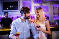 Amis agissant l'un sur l'autre les uns avec les autres au compteur de barre tout en ayant le cocktail Images stock
