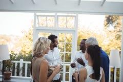 Amis agissant l'un sur l'autre les uns avec les autres tout en ayant le champagne Photos libres de droits