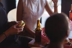 Amis agissant l'un sur l'autre tout en ayant le repas et la bière Images stock