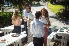 Amis agissant l'un sur l'autre tout en ayant le verre de vin dans le restaurant Image libre de droits