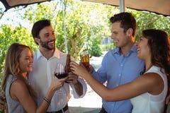 Amis agissant l'un sur l'autre tout en grillant le verre et la bouteille d'alcool au compteur Photographie stock