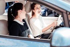 Amis agréables satisfaisants s'asseyant dans la voiture et rire Photos libres de droits