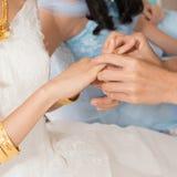 Amis aidant l'anneau de mariage de port d'or de jeune mariée Photographie stock
