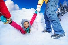Amis aidant la fille à sortir de la caverne de neige Photographie stock