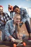 Amis aidant la planche à roulettes élégante d'équitation de fille de hippie Image libre de droits