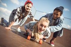 Amis aidant la planche à roulettes élégante d'équitation de fille de hippie Images stock