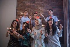 amis allumant des cierges magiques ensemble célébration Image stock