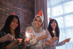 amis allumant des cierges magiques ensemble célébration Photo stock