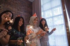 amis allumant des cierges magiques ensemble célébration Photos stock