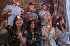 amis allumant des cierges magiques ensemble célébration Photographie stock