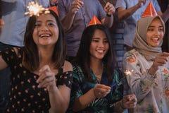 amis allumant des cierges magiques ensemble célébration Images libres de droits
