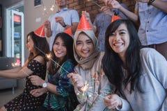 amis allumant des cierges magiques ensemble célébration Images stock
