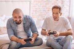 Amis amusés jouant avec la console de jeu sur le lit Images libres de droits