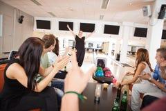 Amis applaudissant pour la femme dans le club de bowling Photographie stock
