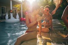 Amis appréciant à la réception au bord de la piscine un jour d'été Image libre de droits