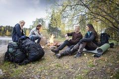 Amis appréciant camper sur au bord du lac Photographie stock libre de droits