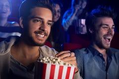 Amis appréciant dans la salle de cinéma Image libre de droits