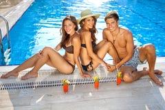 Amis appréciant des boissons à la piscine Photos libres de droits