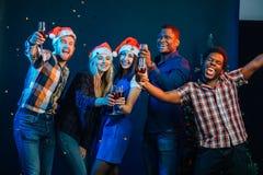 Amis appréciant des boissons de Noël dans la barre Photographie stock libre de droits