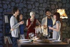 Amis appréciant des boissons par la table de salle à manger Image libre de droits