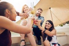Amis appréciant des boissons pendant la partie de dessus de toit Photos libres de droits