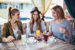 Amis appréciant en conversation et café potable dans c Images stock