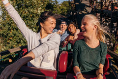 Amis appréciant et encourageant sur des montagnes russes Photos libres de droits