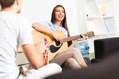 Amis appréciant jouant la guitare et chantant ensemble Images stock