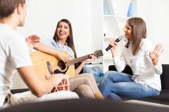 Amis appréciant jouant la guitare et chantant ensemble Image stock