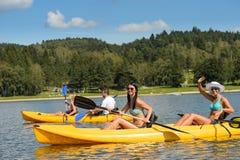 Les jeunes prenant un bain de soleil sur le kayak Photos libres de droits