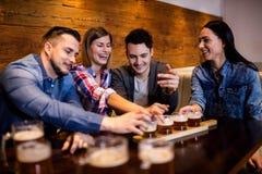 Amis appréciant la bière à la table Images stock
