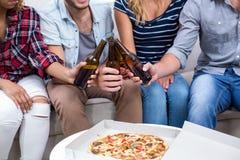 Amis appréciant la bière et la pizza à la maison Photos libres de droits