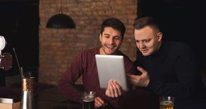 Amis appréciant la bière fraîche au bar et partageant le comprimé Images libres de droits